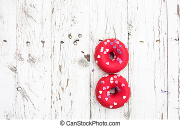 Donuts with heart sprinkles on white wooden background. Donut for bakery menu