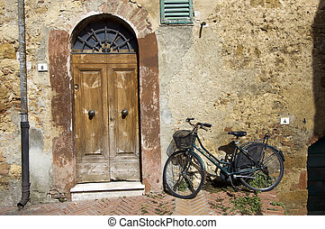 Old wooden door and aged black bycicle. Tuscany Classic.