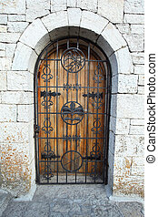 Door behind lattice in stone wall