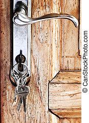 Door handle with keys - Set of keys in lock of old wooden...