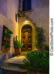 Door in an old house decorated with flower at night