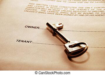 door key on rental agreement - key lying on a lease document