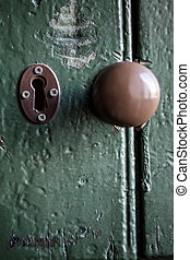 A very old door with the key hole and the knob in the centre.