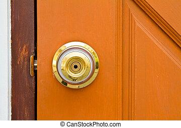 Circle door knob on closed brown wooden door