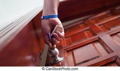 Door knob. The man inserts the key, opens the door and enters the room. Bottom view