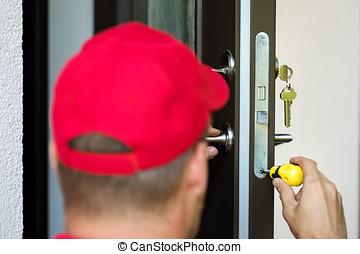 door lock service - locksmith working with screwdriver