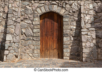 Door - The wooden arched door in the wall of the ragged old...