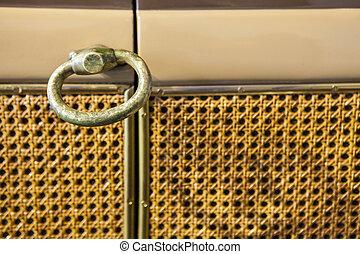 Door with bronze handle and lattice-look weaving cover on
