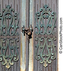DOOR WITH CHAIN AND LOCK - Ornate decorations on a door with...