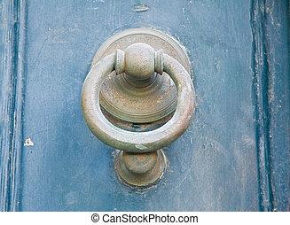 Doorknocker on blue wooden frontdoor.