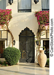 Doors on the building with flowers in summer. Concept for Moroccan and Arabian culture and design