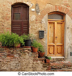 doorsteps decorated with flowerpots to the tuscan house,...