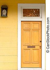 Doorway in a bright yellow building with lantern - A doorway...