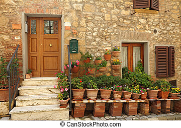 doorway to the tuscan house with lots of flowerpots, Italy