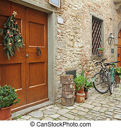 doorway to the tuscan house with christmas wreath and parked bicycles in village Montefioralle near Greve in Chianti, Italy