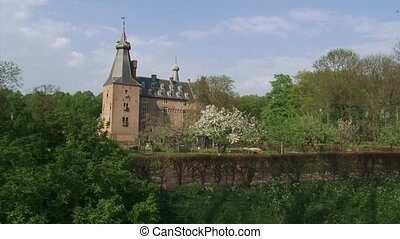 Doorwerth Castle towering above garden and orchard in spring + pan.
