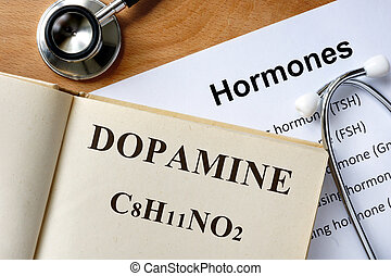 Dopamine  word written on the book and hormones list.