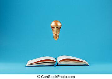 doré, lévitation, idea., concept, arrière-plan., ampoule, cahier bleu, ouvert