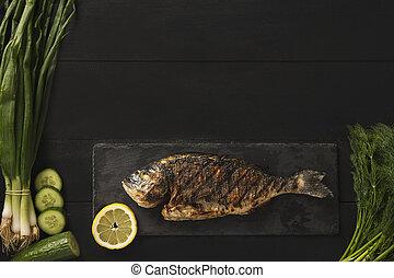 Dorado fish with lemon and fresh vegetables