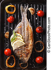 dorado fish with vegetables closeup on the grill. Vertical ...