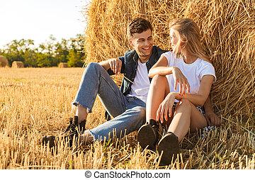 dorato, donna sedendo, foto, coppia, sotto, soleggiato, giovane, campo, grande, durante, mucchio fieno, giorno, uomo
