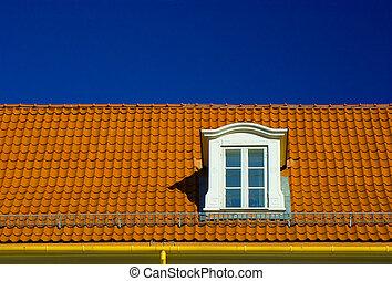 Dormer roof window, in a flashing orange tiled roof on blue...