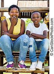 dos, africano, niños, sentado, en, estructura de madera, en, park.