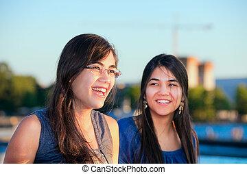 dos, biracial, mujeres jóvenes, sonriente, y, hablar, aire libre