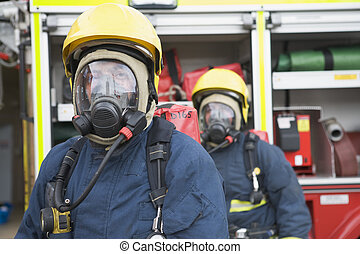 dos, bomberos, en, máscaras, posición, cerca, camión de bomberos, (depth, de, field)