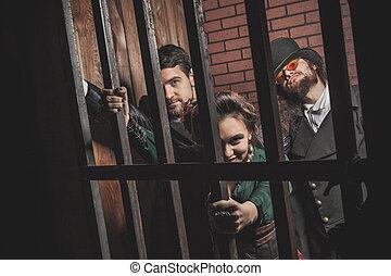 dos, caballeros, y, un, dama, detrás barras, en, el, prison.