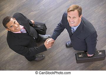 dos, dentro, hombres de negocios, manos, sonriente, sacudida