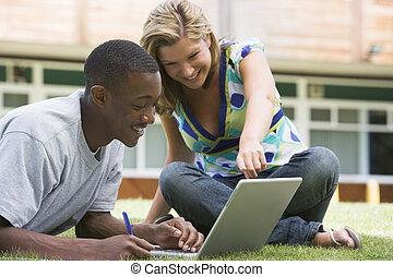 dos, estudiantes, aire libre, en, césped, con, computador portatil