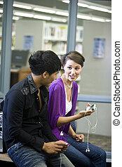 dos, estudiantes de la universidad, con, música, jugadores, en, biblioteca