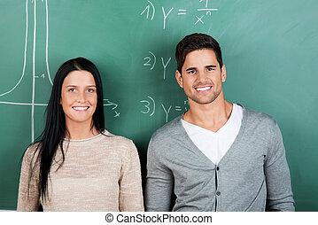 dos, estudiantes, posición, delante de, pizarra