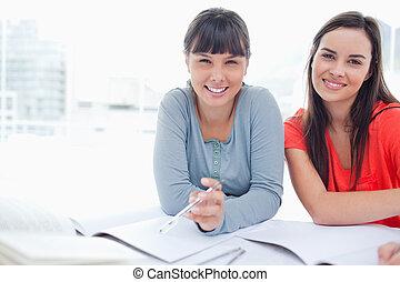 dos, estudiantes, sentado, al lado de, uno al otro, sonriente, como, ellos, trabajo