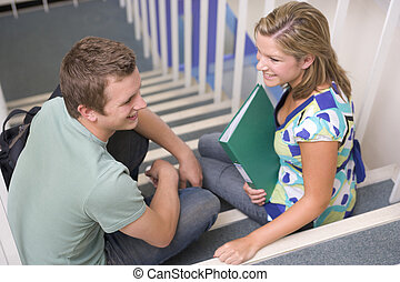 dos, estudiantes, sentar escalera, con, cuadernos, (selective, focus)