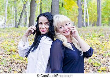 dos, europeo, mujeres que hablan, por, celular, en el estacionamiento