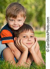 dos, feliz, hermanos, en la hierba