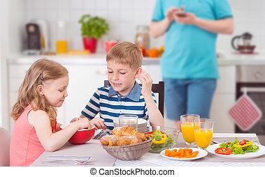 dos, feliz, niños comer, desayuno, durante, padre, trabaja