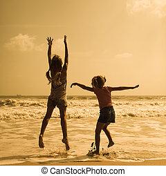 dos, feliz, niños, saltar, en la playa