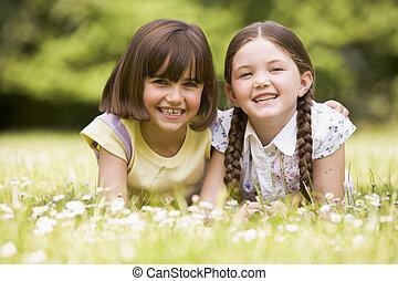 dos, hermanas, acostado, aire libre, sonriente
