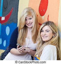 dos, hermoso, colegialas, con, un, teléfono móvil