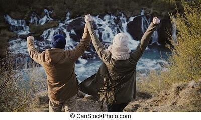 dos, heureux, liberté, couple, mains, iceland., haut, jeune, chutes d'eau, élégant, sentiment, élévation, vue