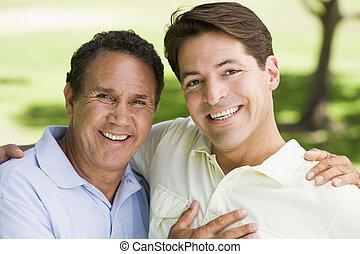 dos hombres, aire libre, se abrazar, y, sonriente
