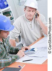 dos hombres, en el escritorio, con, calculadora, teléfono, y, planes