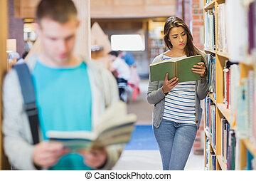 dos, joven, estudiantes, por, estante libros, en, el, biblioteca