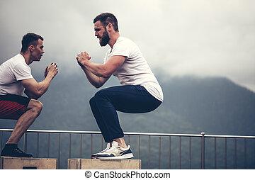 dos, macho, atlético, amigos, hacer, caja, salto, ejercicio, al aire libre, en, montañas