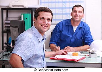 dos, macho, colegas, sentado, en, un, oficina, sonriente, y, mirar, el, cámara