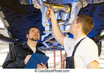dos, mecánica, en, work., dos, confiado, mecánico auto, trabajar, el, taller de reparaciones, mientras, uno, de, ellos, teniendo tablilla sujetapapeles