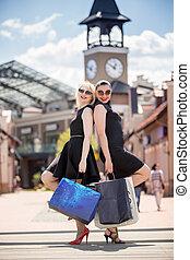 dos, mujer hermosa, posar, con, bolsas de compras, en, calle